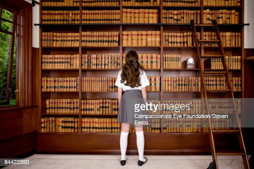 Girl Standing In Front Of Bookshelves In Library Stock
