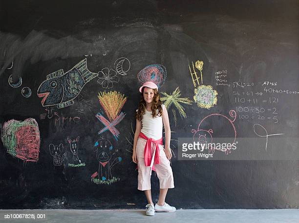 Girl (8-9 years) standing in front of chalkboard, portrait