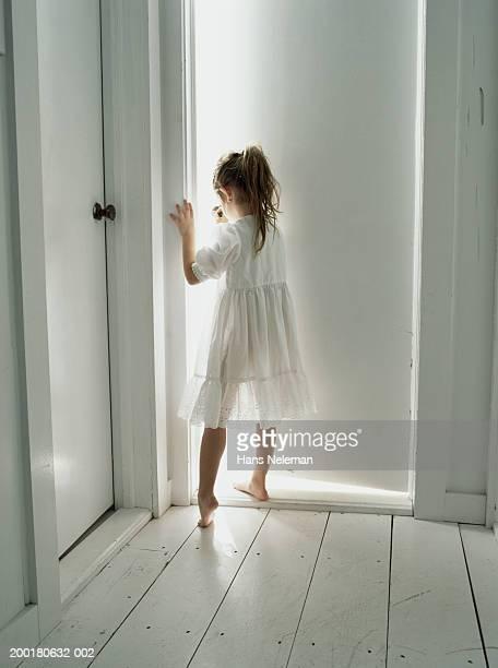 Girl (4-6) standing in front of door,  rear view
