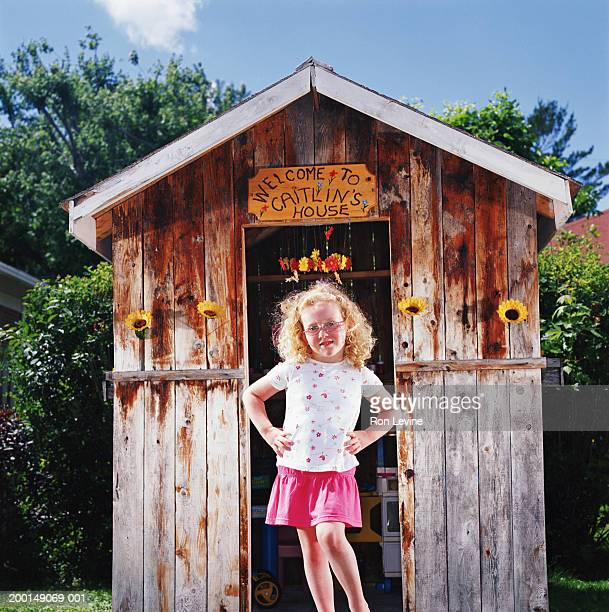 Girl (4-6) standing in front of playhouse, portrait