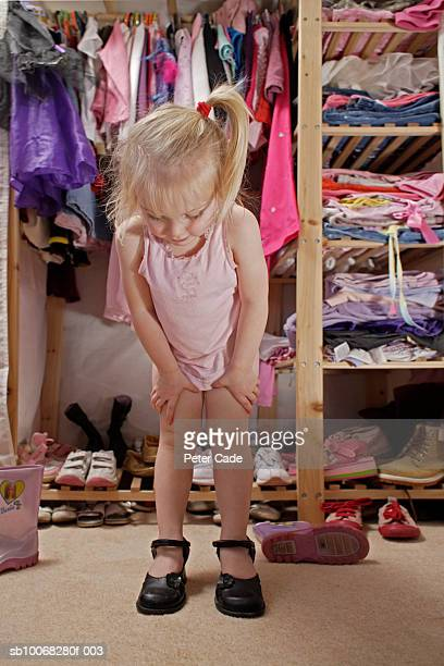 Girl (2-3) standing in front of wardrobe trying on shoes