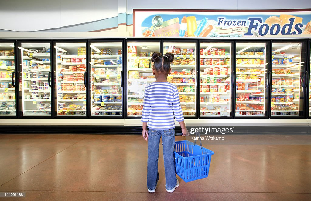 Girl standing in frozen food section. : Stock Photo