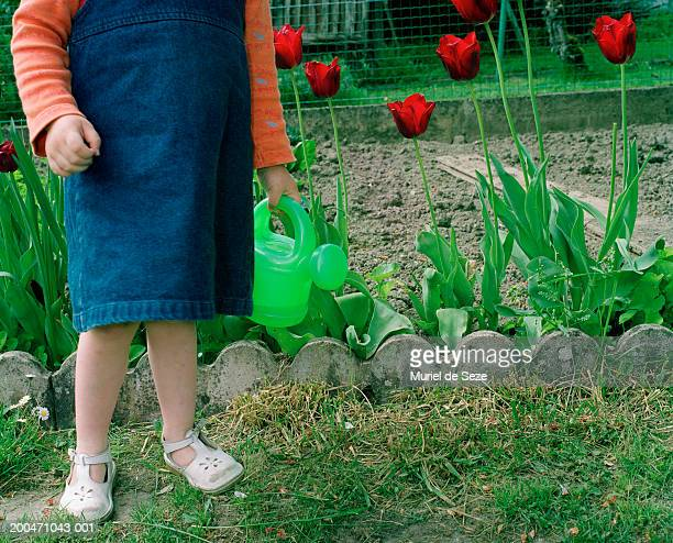 Girl (2-4) standing in garden holding toy watering can, low section