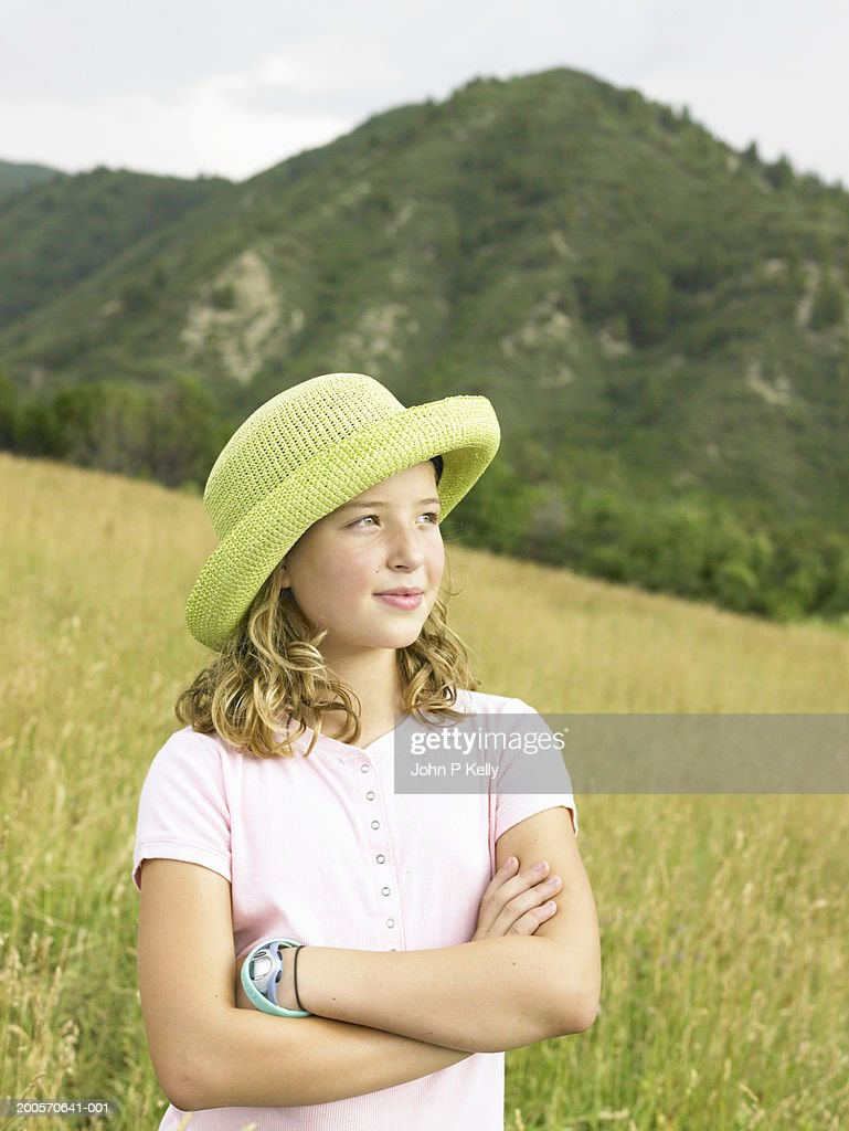 Girl (10-11) standing in grassy field, waist up : Stock Photo