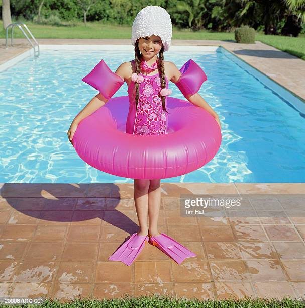 Girl (6-8) standing in inflatable ring by swimming pool, portrait