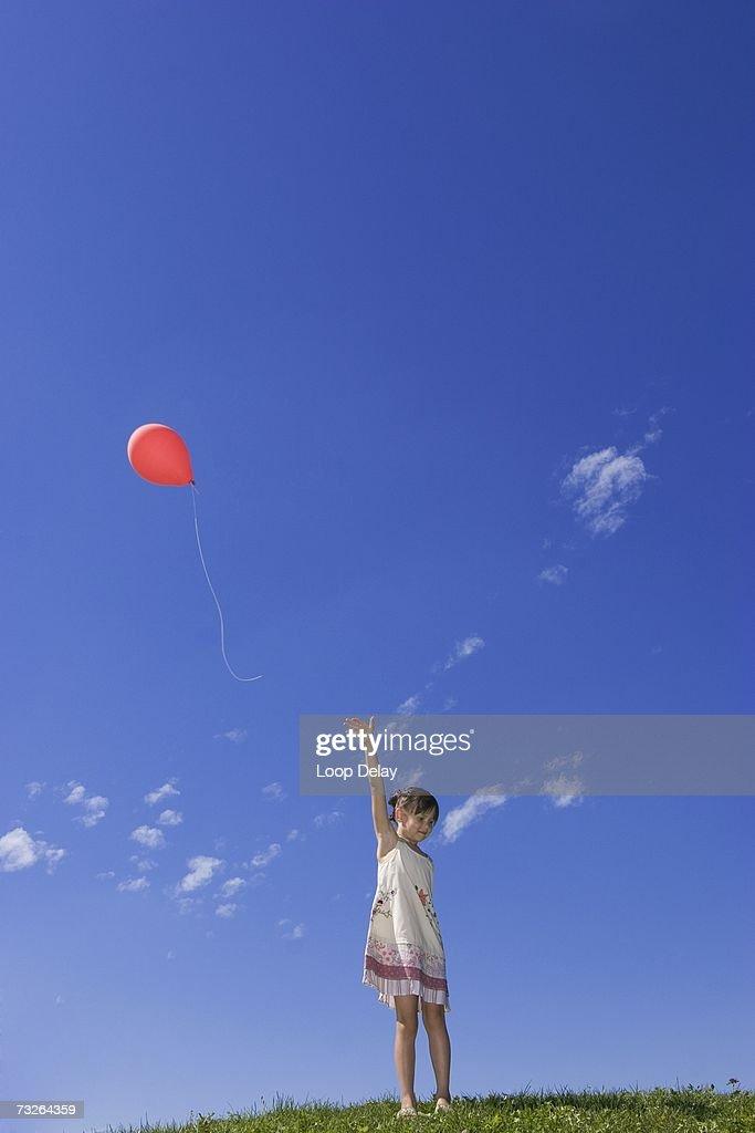 Girl (7-9) standing in meadow, releasing balloon