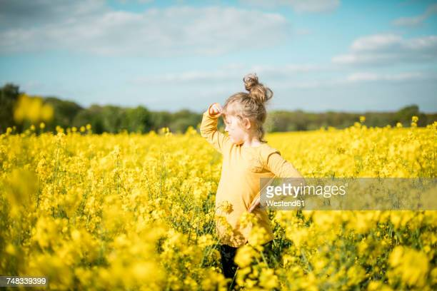 Girl standing in rape field looking out