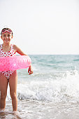 Girl (6-8) standing in sea wearing rubber ring, smiling, portrait
