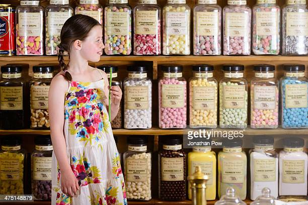 Girl standing in sweet shop in front of shelves of confectionery