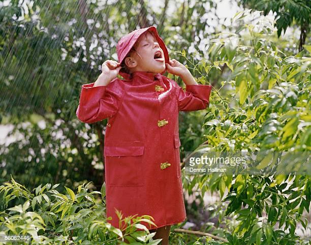 Girl standing in the rain wearing red raincoat