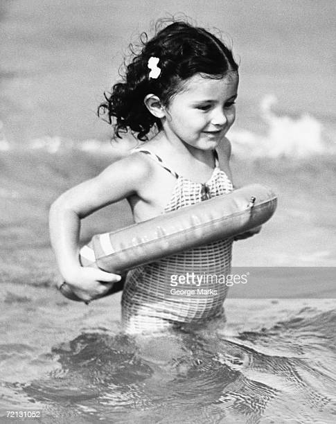 Girl (4-5) standing in water with inflatable ring (B&W)