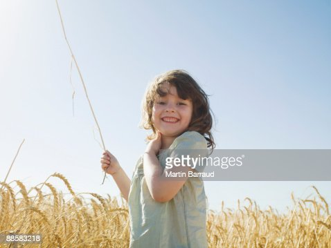 Girl standing in wheat field : Stock Photo