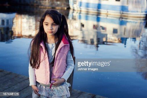 Girl standing near lake : Stock Photo