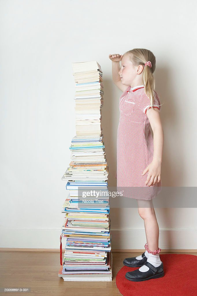 Girl (6-7) standing next to pile of books, measuring height, side view : Stock Photo
