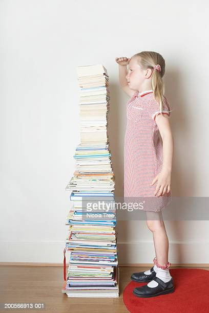 Girl (6-7) standing next to pile of books, measuring height, side view