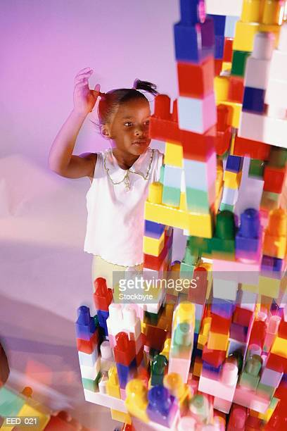 Girl standing next to tower of plastic blocks
