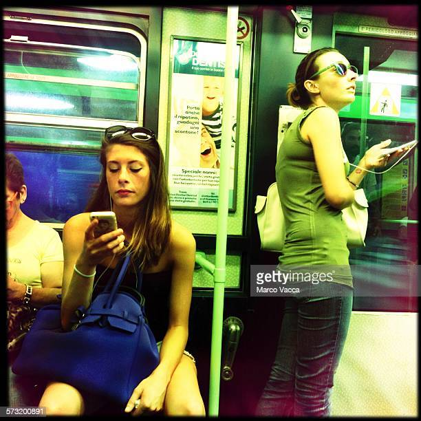 A girl standing on a train connected to her smartphone next to a girl seated while watching the screen of her device Milano Italy