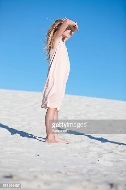 Girl standing on beach looking into the distance
