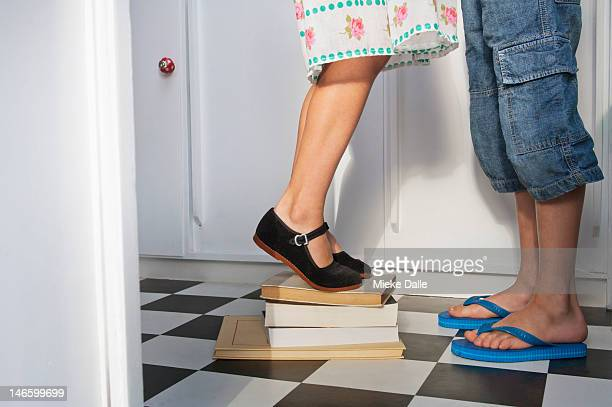 Girl standing on books to kiss a boy