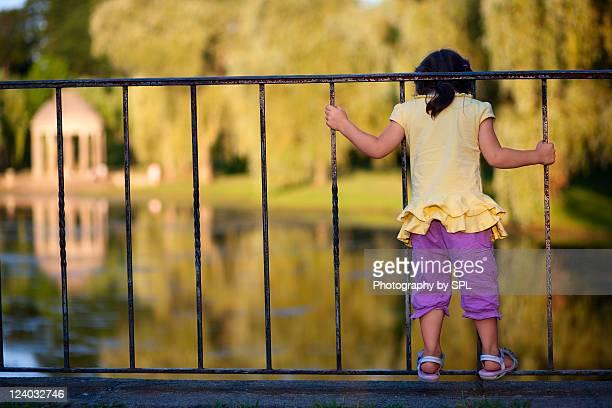 Girl standing on bridge railing