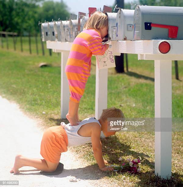 Girl standing on brother's back and peering into mailbox