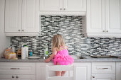 Girl standing on chair at kitchen counter