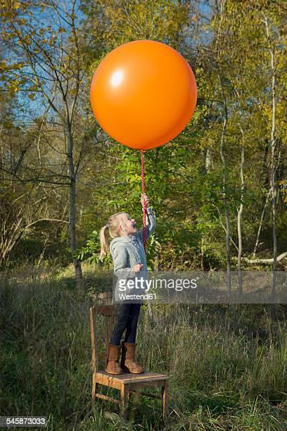 Girl standing on chair holding balloon on meadow
