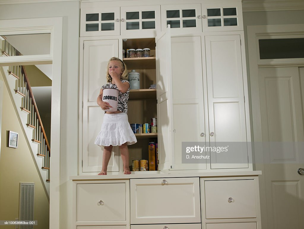 Girl (4-5) standing on counter in kitchen, eating cookies from jar