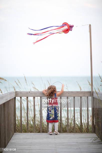 Girl standing on deck near ocean
