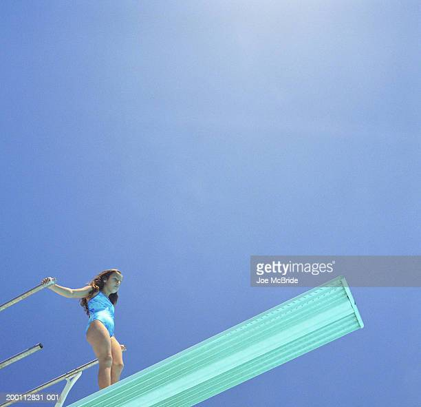 Girl (8-10) standing on diving board, low angle view