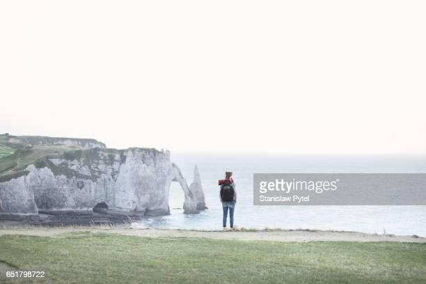 Girl standing on edge of cliff