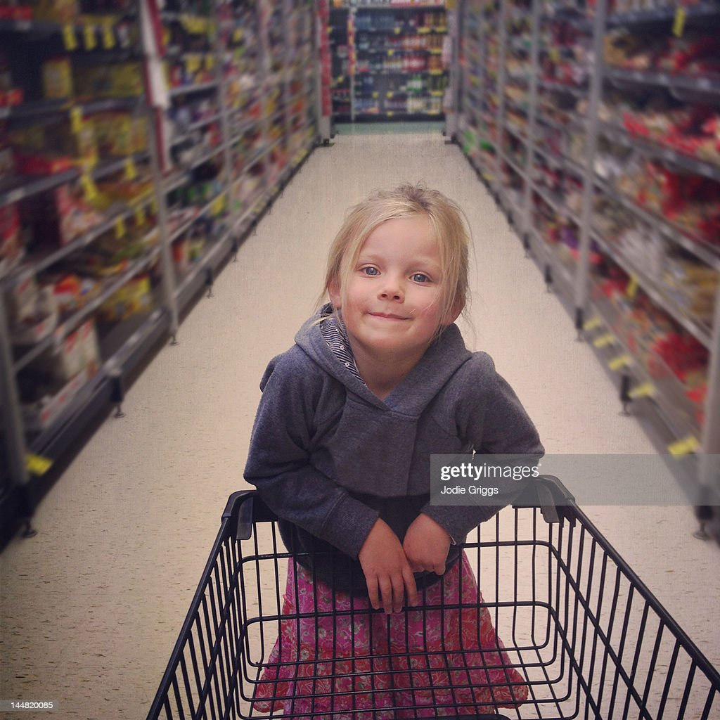 Girl standing on end of shopping trolley : Stock Photo