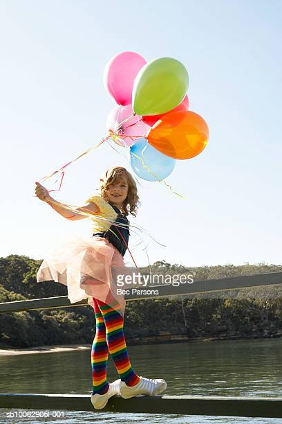 Girl (8-9) standing on fence by river, holding balloons, portrait