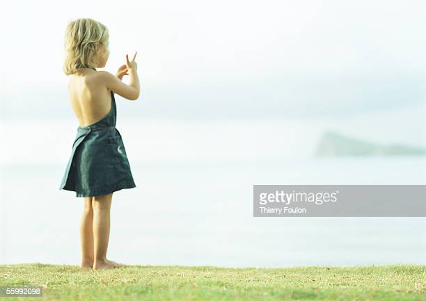 Girl standing on grass, rear view