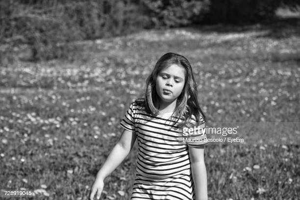 Girl Standing On Grassy Field
