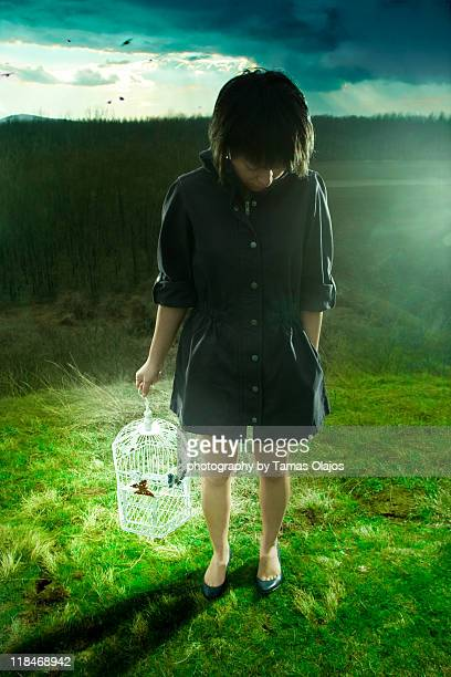 Girl standing on hill holding lighting birdcage