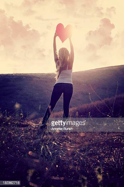 Girl standing on hill with heart