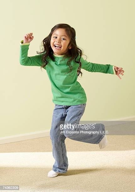 Girl (4-5) standing on one leg, laughing