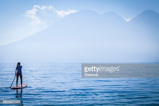 Girl standing on paddleboard in remote lake