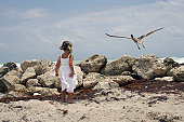 Girl (4-5) standing on seashore, looking at bird taking off, rear view