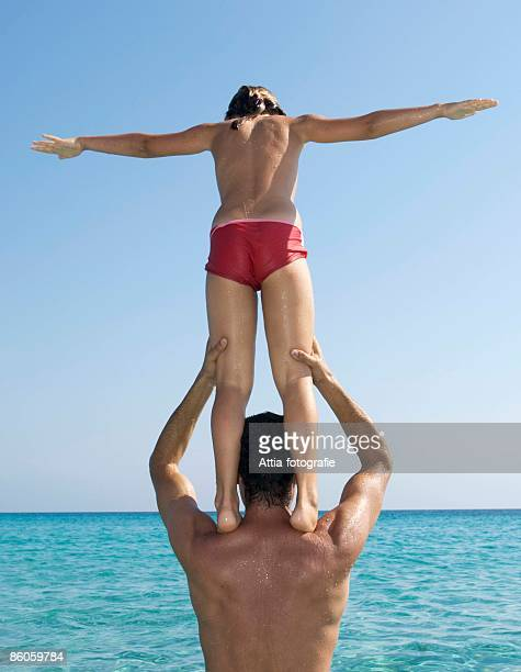 Girl standing on shoulders of father by sea