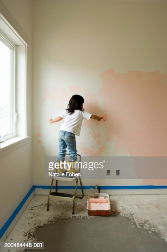girl painting bedroom wall rear view stock photo getty images