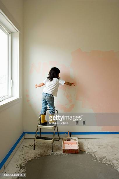 Girl (4-6) standing on step ladder, painting bedroom wall, rear view