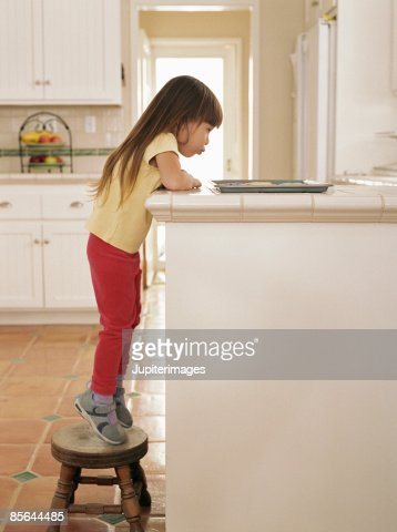 Girl standing on stepstool looking at cookies : Stockfoto
