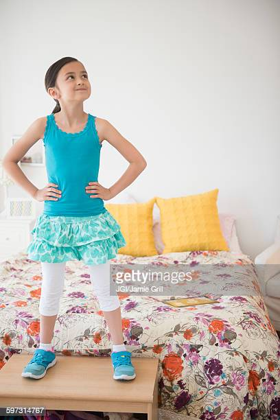 Girl standing on table near bed