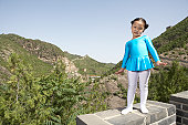 A girl standing on the Great Wall of China.