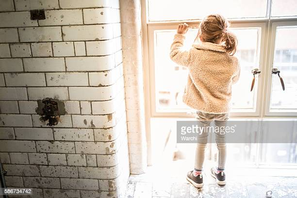 Girl standing on the window sill watching outside