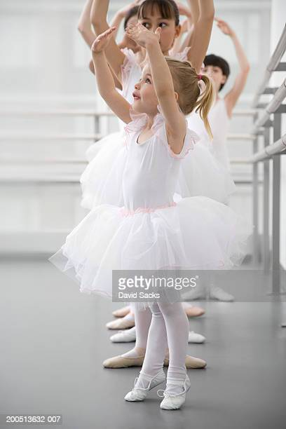 Girl (2-4) standing on tip toes in ballet class