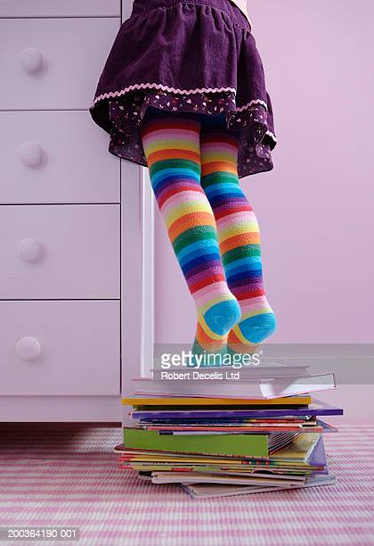 Girl (3-5) standing on tip toes on pile of books, low section
