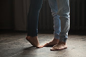 Barefoot girl standing on tiptoe to hug her man at home, sweet cute romantic couple kissing concept, male and female legs feet wearing jeans close up view, warm floor heating, femininity and delicacy